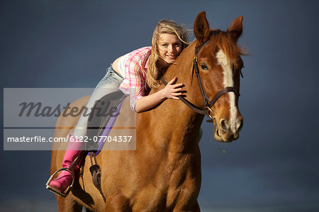 Teenage girl riding horse outdoors Stock Photo - Premium Royalty-Free, Image code: 6122-07704337