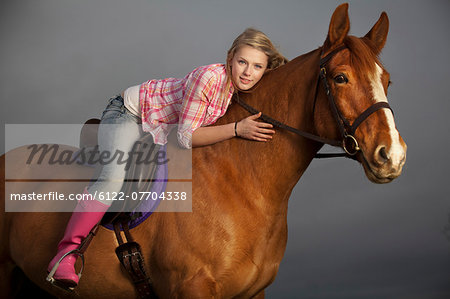 Teenage girl riding horse outdoors Stock Photo - Premium Royalty-Free, Image code: 6122-07704338