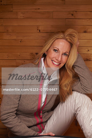 Smiling woman sitting on wooden bench Stock Photo - Premium Royalty-Free, Image code: 6122-07704467