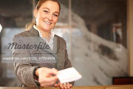 Hotel concierge with card at desk Stock Photo - Premium Royalty-Free, Image code: 6122-07704474