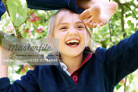 Smiling children climbing tree together Stock Photo - Premium Royalty-Free, Image code: 6122-07704848