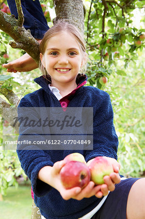 Smiling girl offering fruit in tree Stock Photo - Premium Royalty-Free, Image code: 6122-07704849