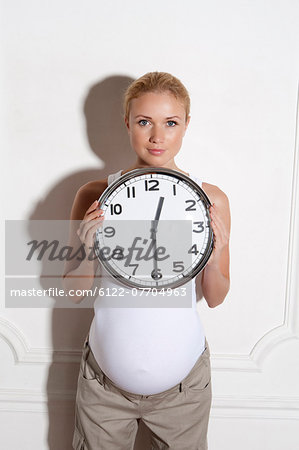 Pregnant woman holding clock Stock Photo - Premium Royalty-Free, Image code: 6122-07704963