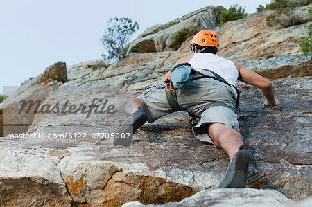 Climber scaling steep rock face Stock Photo - Premium Royalty-Free, Image code: 6122-07705007