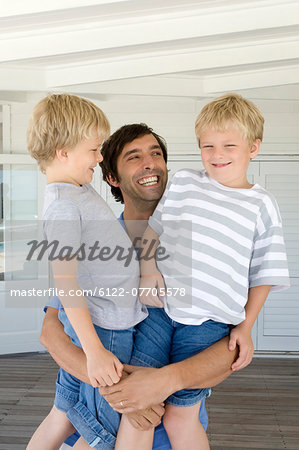 Smiling father holding sons Stock Photo - Premium Royalty-Free, Image code: 6122-07705578