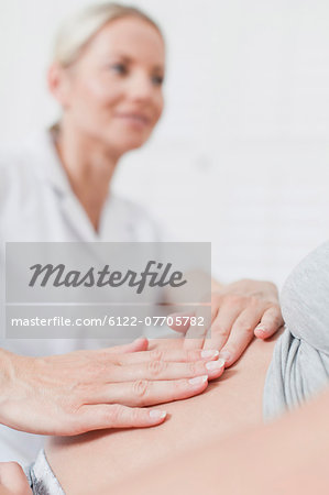 Doctor examining pregnant womans belly Stock Photo - Premium Royalty-Free, Image code: 6122-07705782