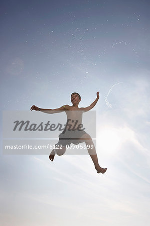 Boy posing in mid-air Stock Photo - Premium Royalty-Free, Image code: 6122-07705999