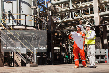 Workers talking at oil refinery Stock Photo - Premium Royalty-Free, Image code: 6122-07706231