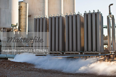 Machinery and smoke at oil refinery Stock Photo - Premium Royalty-Free, Image code: 6122-07706261