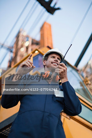 Worker using walkie talkie on site Stock Photo - Premium Royalty-Free, Image code: 6122-07706263