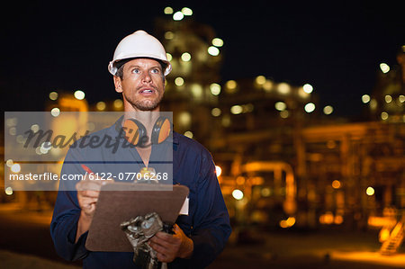 Worker with clipboard at oil refinery Stock Photo - Premium Royalty-Free, Image code: 6122-07706268