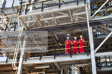 Workers standing on ledge together Stock Photo - Premium Royalty-Free, Image code: 6122-07706273