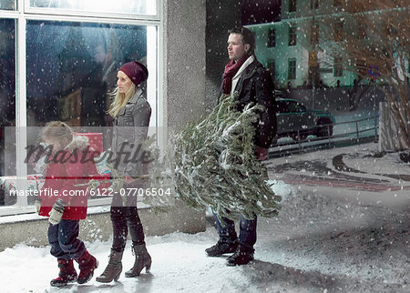 Family carrying Christmas tree in snow Stock Photo - Premium Royalty-Free, Image code: 6122-07706504