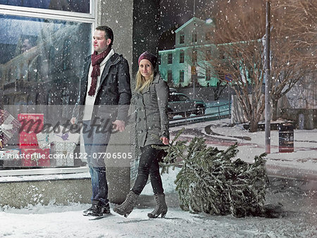 Couple carrying Christmas tree in snow Stock Photo - Premium Royalty-Free, Image code: 6122-07706505