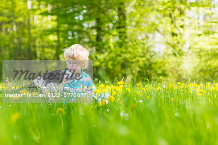 Boy with dog in field of tall grass Stock Photo - Premium Royalty-Free, Image code: 6122-07706771