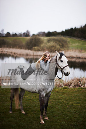 Girl laying on horse in field Stock Photo - Premium Royalty-Free, Image code: 6122-07706958