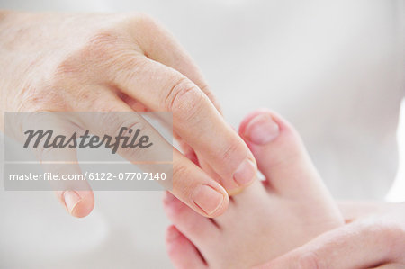Close up of masseuse working on feet Stock Photo - Premium Royalty-Free, Image code: 6122-07707140