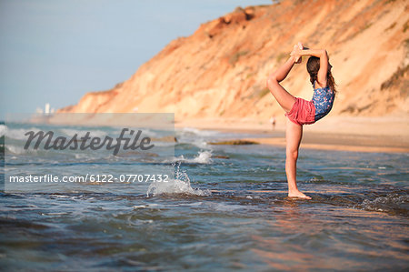 Woman practicing yoga on beach Stock Photo - Premium Royalty-Free, Image code: 6122-07707432