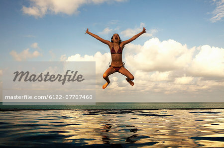 Girl jumping into infinity pool Stock Photo - Premium Royalty-Free, Image code: 6122-07707460