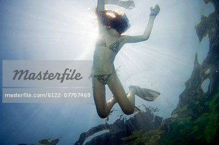 Girl snorkeling in tropical waters Stock Photo - Premium Royalty-Free, Image code: 6122-07707469