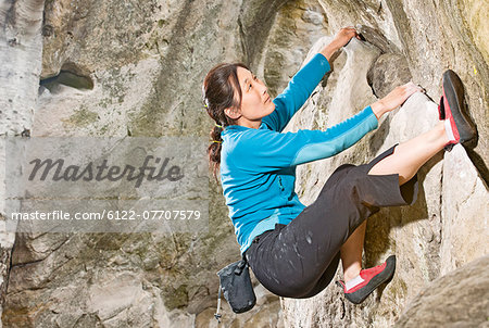 Climber scaling steep rock face Stock Photo - Premium Royalty-Free, Image code: 6122-07707579