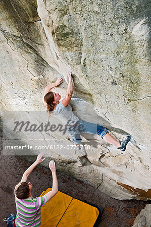Climber spotting woman on steep cliff Stock Photo - Premium Royalty-Free, Image code: 6122-07707581