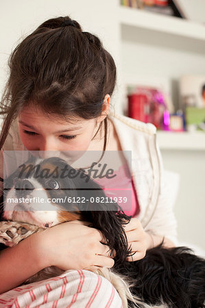 teenage girls playing with dog at home Stock Photo - Premium Royalty-Free, Image code: 6122-08211939