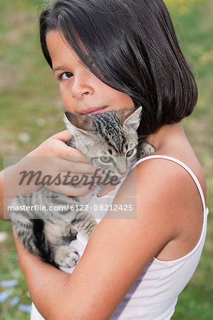 Girl holding pet cat, portrait Stock Photo - Premium Royalty-Free, Image code: 6122-08212425
