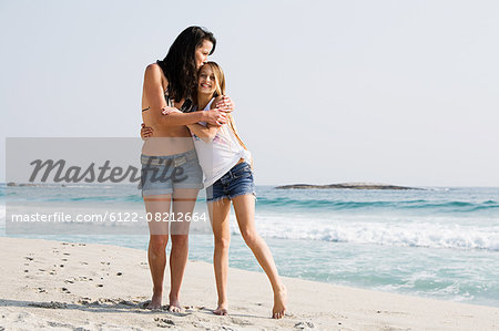 Mother and daughter hugging on a beach Stock Photo - Premium Royalty-Free, Image code: 6122-08212664