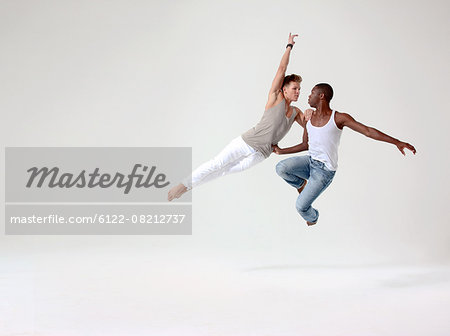 Two young men in mid air Stock Photo - Premium Royalty-Free, Image code: 6122-08212737