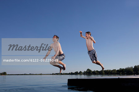 Father and son jumping into lake Stock Photo - Premium Royalty-Free, Image code: 6122-08229045