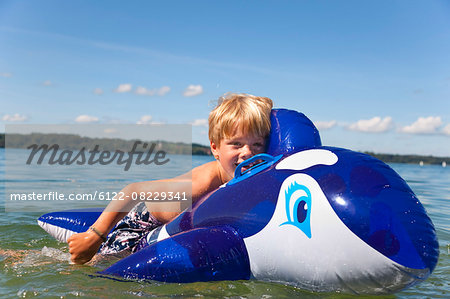 Boy floating in lake with toy whale Stock Photo - Premium Royalty-Free, Image code: 6122-08229341