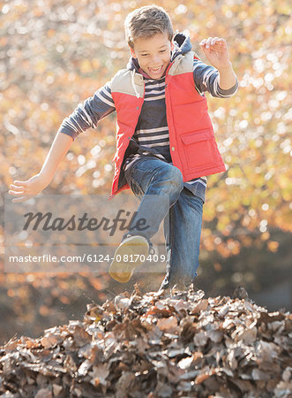 Enthusiastic boy jumping over pile of autumn leaves Stock Photo - Premium Royalty-Free, Image code: 6124-08170409