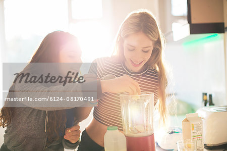Teenage girls making smoothie in sunny kitchen Stock Photo - Premium Royalty-Free, Image code: 6124-08170491