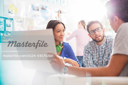 Creative business people discussing paperwork in office Stock Photo - Premium Royalty-Free, Image code: 6124-08170788