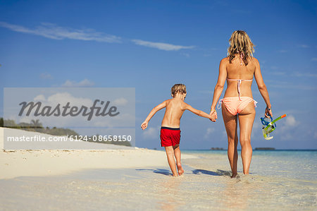 Mother and son walking on sunny tropical beach Stock Photo - Premium Royalty-Free, Image code: 6124-08658150