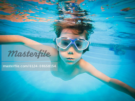 Portrait of boy swimming underwater in swimming pool Stock Photo - Premium Royalty-Free, Image code: 6124-08658154