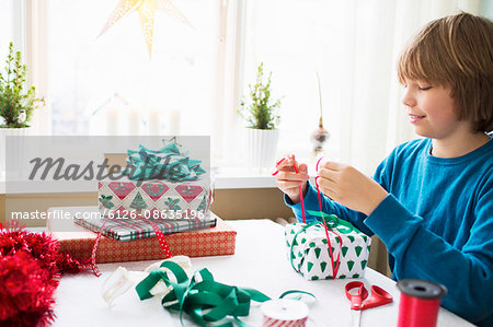 Boy (10-11) wrapping Christmas presents