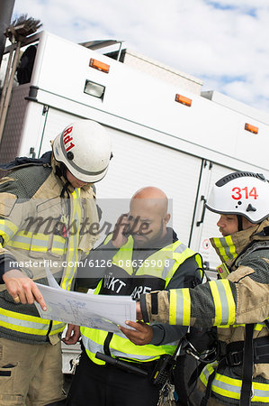 Sweden, Sodermanland, Security guard and firefighters looking at plan Stock Photo - Premium Royalty-Free, Image code: 6126-08635908