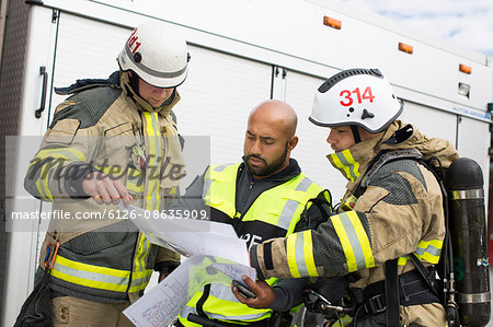 Sweden, Sodermanland, Security guard and firefighters looking at plan Stock Photo - Premium Royalty-Free, Image code: 6126-08635909
