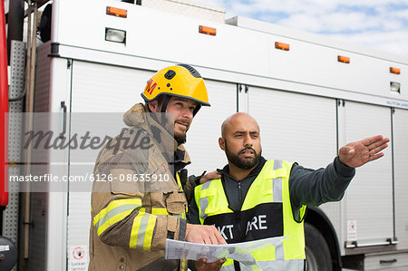 Sweden, Sodermanland, Security guard and firefighter discussing plan Stock Photo - Premium Royalty-Free, Image code: 6126-08635910