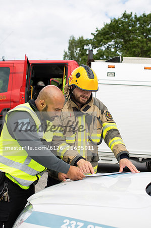Sweden, Sodermanland, Security guard and firefighter discussing plan Stock Photo - Premium Royalty-Free, Image code: 6126-08635911