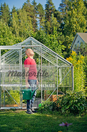 Finland, Paijat-Hame, Heinola, Man standing outside greenhouse and holding watering can Stock Photo - Premium Royalty-Free, Image code: 6126-08636523