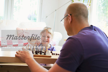 Father learning daughter (6-7) play chess Stock Photo - Premium Royalty-Free, Image code: 6126-08636536