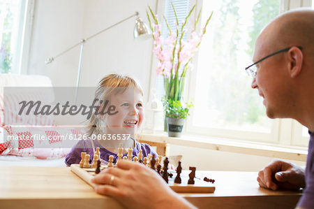 Father learning daughter (6-7) play chess Stock Photo - Premium Royalty-Free, Image code: 6126-08636537