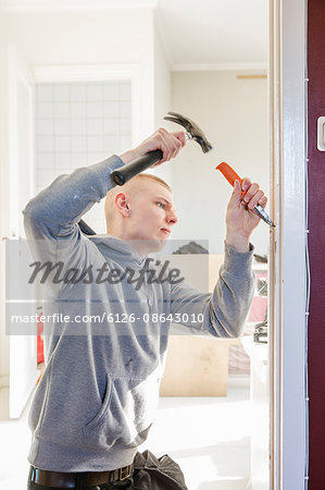 Sweden, Young man renovating house Stock Photo - Premium Royalty-Free, Image code: 6126-08643010