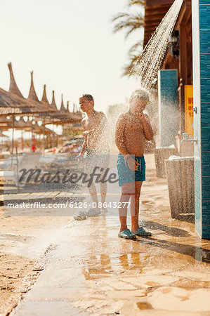 Turkey, Alanya, Boy (10-11) and girl (8-9) standing under shower on beach Stock Photo - Premium Royalty-Free, Image code: 6126-08643277