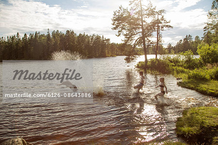 Sweden, Narke, Kilsbergen, Bjorktjarn, young man with children (10-11, 12-13) playing in lake at sunset Stock Photo - Premium Royalty-Free, Image code: 6126-08643886
