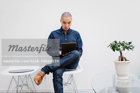 Sweden, Freelancer sitting with digital tablet Stock Photo - Premium Royalty-Free, Image code: 6126-08644039