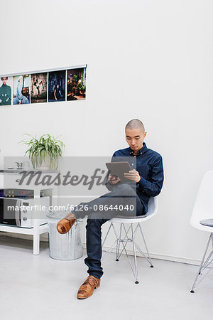 Sweden, Freelancer sitting with digital tablet Stock Photo - Premium Royalty-Free, Image code: 6126-08644040
